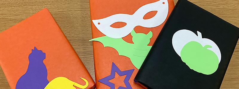 Picture of books covered in orange paper covered with Halloween-themed cut outs